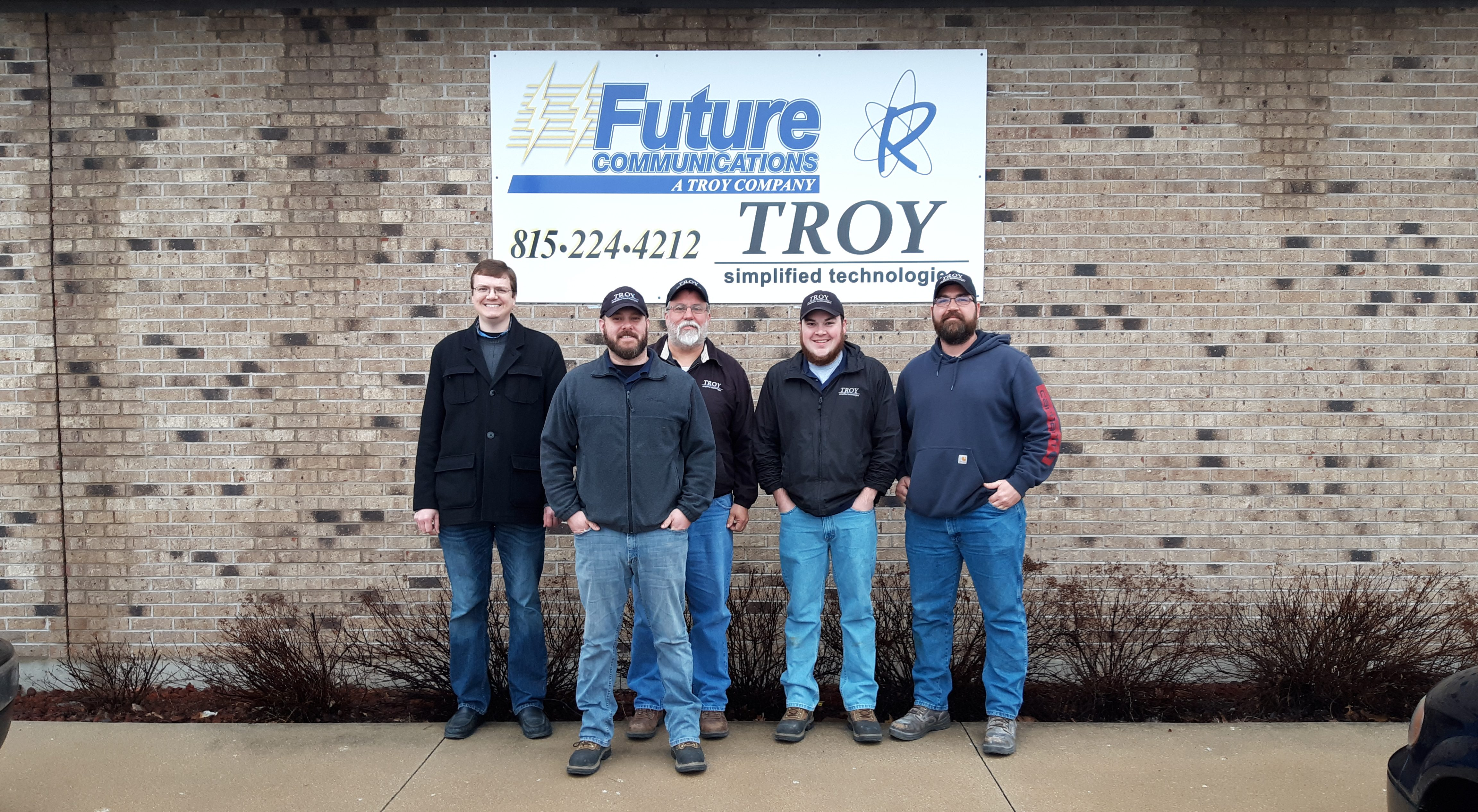 Troy Simptech employees, smiling in front of their logo.